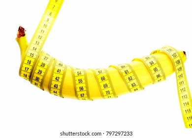 Banana with yellow tape for measuring waist and figure. Weight loss and dieting concept. Yellow tape around banana isolated on white background. Centimeter ruler and fresh fruit. Healthy food concept.