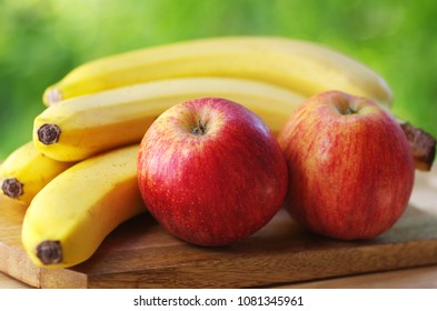 bananas and apples on green background