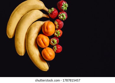 Bananas, apricots and strawberries against a black background with reflection