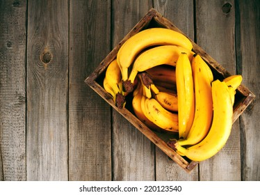 Bananas in a box on a wooden background.