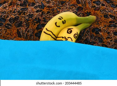 Bananas hugging each in bed. He is happy, she is sad.