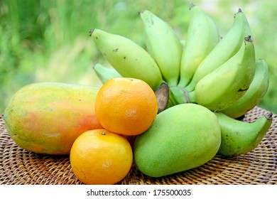 Bananas, mango, oranges and papaya from organic orchard in closed-up with natural green background.
