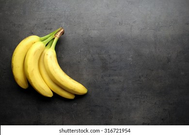 Bananas on grey kitchen table with copyspace