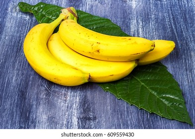bananas on a leaf upon a wooden table