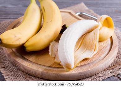 Bananas and peeled banana on a cutting board