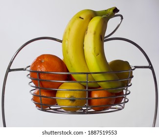 Bananas, satsumas, an orange and some lemons in a metal wire bowl.