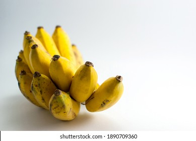 Bananas start to ripen and bruise on a white background.
