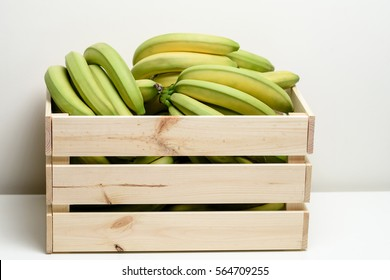 Bananas in wooden box, isolated on white background