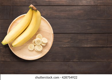 Bananas in a wooden dish on a wooden background. Copy space for text on wooden background.