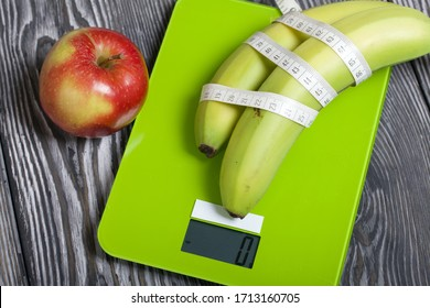 Bananas wrapped in measuring tape lie on the scales. Near apples. Scales show zero. On brushed pine boards. Symbol of World No Diet Day.