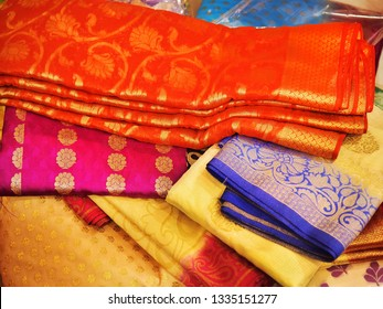 Banares silk saris in a textile shop,  displayed in front of customers. These exquisite, expensive sarees are famous for their gold and silver zari, brocade.
