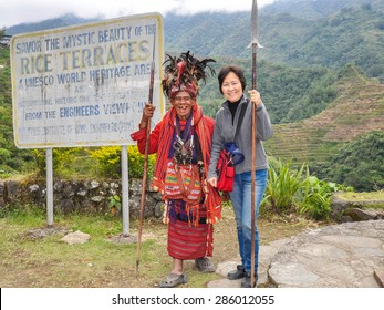 Banaue, Philippines - Feb. 28, 2014: Igorot and unidentified tourist. The Igorots are one of the indigenous peoples of the Philippines who inhabit the mountains of the country's main island of Luzon.
