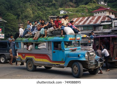 Banaue, Philippines - June 17, 2009: Typical Jeepney overloaded with passengers near Banaue, Philippines. Jeepneys are both cheap public transportation and the symbol of Philippine culture and art