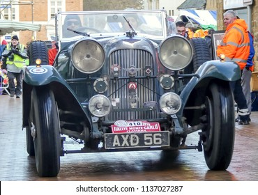 Banbury, Oxfordshire. England - February 1 2018: Entrant 410 in Classic Monte Carlo Rally, a 1930's Lagonda 4.5 litre sports car. Driving just after start of the event. Spectators in the street.