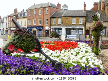 Banbury, Oxfordshire. England -July 22, 2018: Floral Remembrance tribute of centenary of the end of the Great War. Hobby horse with poppy in foreground. On a roundabout with retail shops in background