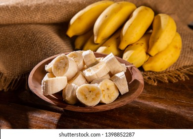 A banch of bananas and a sliced banana on wood background.