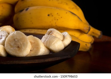 A banch of bananas and a sliced banana in a pot over a table