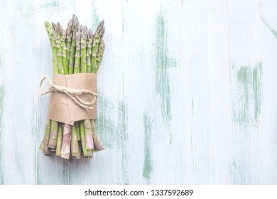 banches of fresh green asparagus on concret background, top view