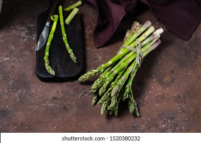 Banches of fresh green asparagus on dark background