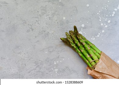 banches of fresh green asparagus on gray stone table with rosemary and sage. asparagus recipe, top view