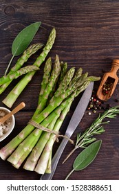 banches of fresh green asparagus on wooden background with rosemary and sage. asparagus recipe, top view
