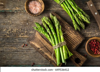 banches of fresh green asparagus on wooden background, top view