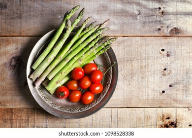 Banches of fresh green asparagus and tomatoes
