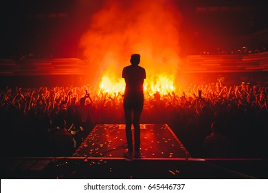 Band on stage.  Music show. Bright scene lighting in club. Fans burn red flares at rock concert. View from the stage to the vocalist. Russian punk rock band.