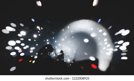 band perform concert on stage of nightclub.  Dark background, smoke, concert  spotlights, lensbaby effect