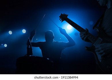 Band performing live during concert, gig. Guitarist and drummer silhouettes - Shutterstock ID 1911384994