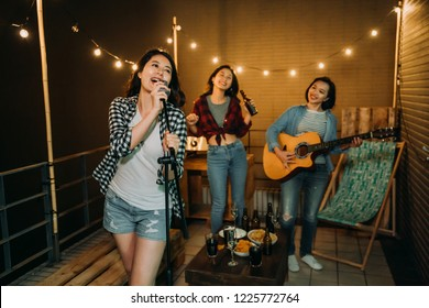 band playing music practicing songs on roof. young girls love music enjoy in karaoke party outdoor on rooftop at night. food and alcohol drinks on table beside comfortable desk chair.