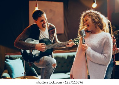 Band practice for the show. Woman with curly hair holding microphone and singing while man in background playing acoustic guitar. Home studio interior.