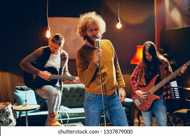 Band practicing for the gig.  Male singer with curly hair holding microphone and singing. In background band playing instruments. Home studio interior.