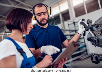 Band saw cutting machine operator taking with stock clerk in factory warehouse