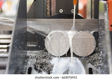 The band saw cutting the steel rod with the coolant