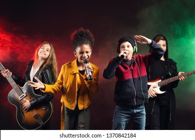 Band of teenage musicians on dark background