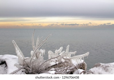 A band of winter evening light dividing steel-gray clouds from a steel-gray lake with frozen branches and snow on shore in the foreground.