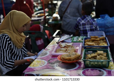 Banda Aceh, Indonesia - May 30, 2018: Vendor selling variety of local cakes and dessert during fasting month at Street market food in Banda Aceh, Indonesia