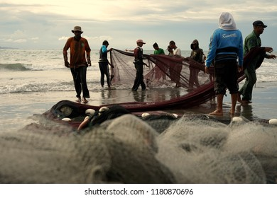 Banda Aceh, Aceh, Indonesia - September 16, 2018: Group of fishermen manually pulls their net out from the ocean at Gampong Jawa Beach, Banda Aceh