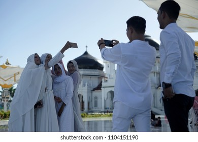 Banda Aceh, Aceh Province / Indonesia - June 3 2018 :Tourists are taking pictures/selfie in front of Baiturrahman grand mosque in Banda Aceh, Indonesia.