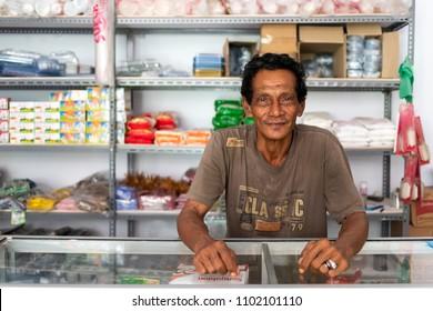 BANDA NEIRA, MALUKU ISLANDS, INDONESIA, DECEMBER 19, 2017 : Portrait of a cheerful local convenient store seller in Banda Neira, Maluku islands, Indonesia.