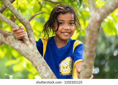 BANDA NEIRA, MALUKU ISLANDS, INDONESIA, DECEMBER 17, 2017 : Portrait of a smiling sweet little girl climbing at a tree in Banda Neira, Maluku islands, Indonesia.