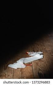 Bandage fallen on wooden floor in strip of light. Top view.