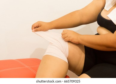 Bandage onto overweight woman leg.