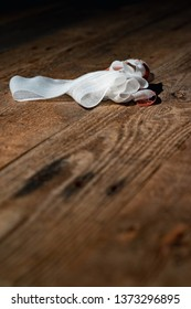 Bandage with tape fallen on wooden floor.