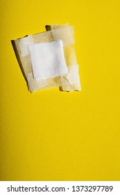 Bandage with tape fallen on yellow floor. Top view.