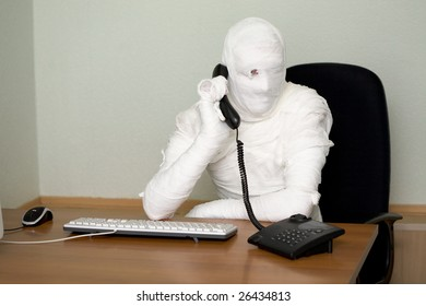 Bandaged boss calling on telephone in office