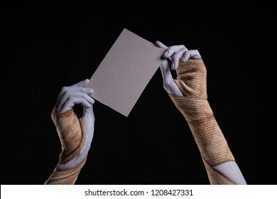 Bandaged mummy hands holding a piece of cardboard, Halloween theme