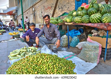 Bandar Abbas, Hormozgan Province, Iran - 16 april, 2017: Two persian men sell vegetables and fruits sitting on the sidewalk under the open sky.