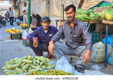 Bandar Abbas, Hormozgan Province, Iran - 16 april, 2017: Two Iranian fruit traders are sitting on the sidewalk near their product.